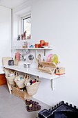 Play kitchen made from shelves on white wall in child's bedroom