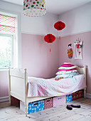 Boxes below bed in child's bedroom decorated in pink