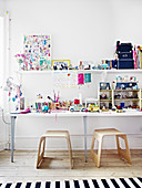 Two stools below table of toys in children's bedroom decorated in white
