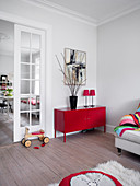 Red metal sideboard and ride-on toy in living room