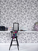 High chair at floating desk against floral wallpaper