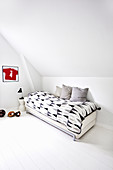 Blanket with graphic pattern on bed in minimalist child's bedroom