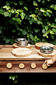 Child's hands turning wooden oven control of outdoor play kitchen