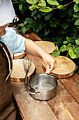 Child seasoning pan of pretend food on hob made from wooden discs in outdoor play kitchen
