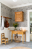 Wooden table below old wooden cabinet on wall with patterned wallpaper