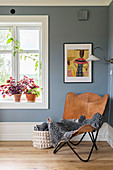 Sheepskin rug on leather easy chair against grey wall and next to window with potted Coleus on windowsill