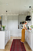 Woman in open-plan kitchen with elegant pale-grey panelled cabinets