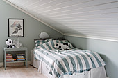 Bed with striped bed linen in child's bedroom with sloping ceiling