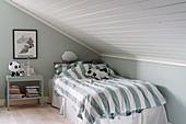 Gestreifte Bettwäsche auf dem Bett im Kinderzimmer unter der Schräge