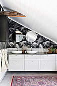 Twin sinks on washstand in elegant bathroom with sloping ceiling