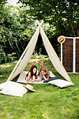 Two girls playing in tent behind floor cushions in garden