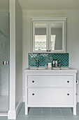 Washstand below mirrored wall cabinet in bathroom