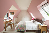 Double bed and desk in attic bedroom with pink walls