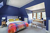 Double bed and desk in attic bedroom with blue walls