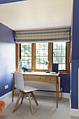 Desk below lattice window in room with blue walls