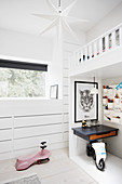 Ride-on toys and desks below white loft bed in child's bedroom