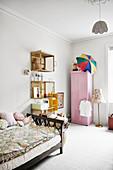 Bett, Wandregale aus alten Kisten und rosa Kleiderschrank im Mädchenzimmer