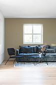Graues Polstersofa, Stuhl und Couchtisch im Wohnzimmer mit olvigrüner Wand