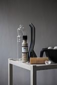 Küchenutensilien Salzmühle, Flasche und Eier auf grauem Tisch