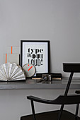 Framed motto and camera on grey desk with black chair