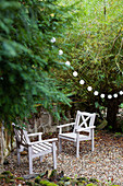 Two wooden chairs and fairy lights in garden