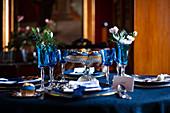 Blaue Gläser und Teller auf festlich gedecktem Tisch mit Blumen