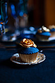 Perfectly decorated cupcake with blue icing and gold rose