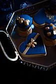 Cupcakes und Plätzchen mit Topping in Dunkelblau und Gold