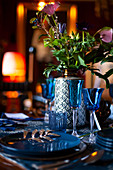Blue glasses and plates and vase of flowers on festively set table