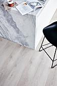 Barstools at modern, marble kitchen island on wooden floor