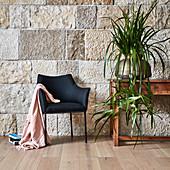 Schwarzer Polsterstuhl und Konsolentisch mit Pflanze vor Steinwand