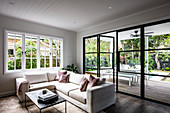 Cream sofa next to glass wall leading to terrace and garden