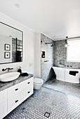 Freestanding bathtub in elegant bathroom in grey, black and white