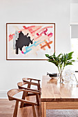 Abstract painting above modern wooden dining table