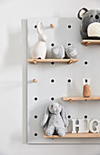Baby toys in shades of grey on shelves on peg board