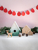 Winterdekoration mit Nisthäuschen, Zapfen, Rentierfigur und Girlande