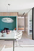 Dining table in front of upholstered niche in wall in modern, architect-designed house