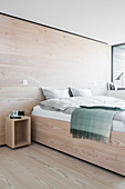 Bed in bedroom with pale wooden floor and walls