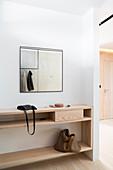 Sideboard aus hellem Holz und Spiegel im Eingangsbereich