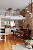 Bett auf der Zwischenebene im Apartment mit offener Küche