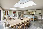 Country-house kitchen and dining table below skylight in spacious open-plan interior