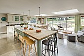 Country-house kitchen and seating area below skylights and glass sliding doors leading to terrace