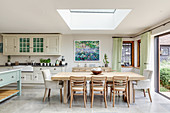 Dining table below skylight and country-house kitchen in open-plan interior