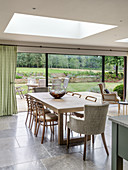 Dining table in bright interior with skylight and wide, glass sliding doors leading to terrace