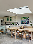 Dining table positioned below skylight and country-house kitchen in open-plan interior