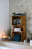 DIY shelves making from wooden crates in bathroom with stone wall