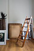 Old wooden stepladder in front of pictures leaning against grey wall