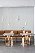 Designerstühle und kleine Tische an Lederbank im Restaurant