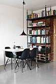 Schwarze Schalenstühle am Esstisch, Bücherregal vor Backsteinwand