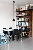 Hellblauer Kinderstuhl und schwarze Schalenstühle am Esstisch